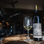 Skeleton Root wine bottle with glass of wine