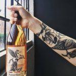 tattooed arm holding Skeleton Root wine bottle