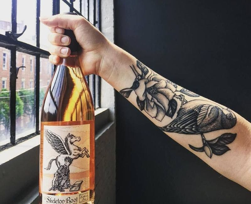tattooed arm holding Skeleton Root wine bottle