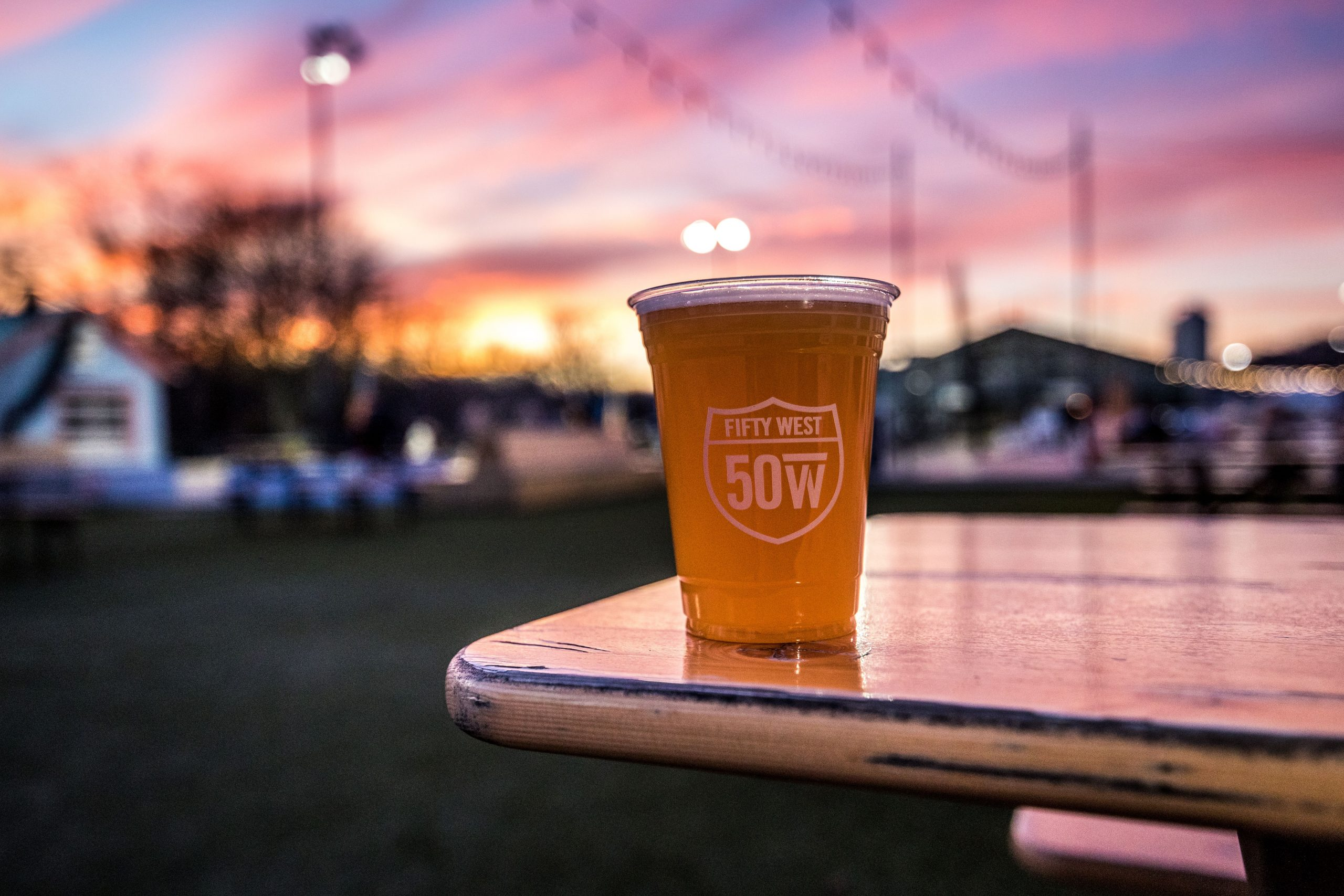 50 West brewery cup of beer with sunset
